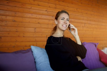 Happy woman having pleasant cell telephone conversation with her boyfriend, while is sitting in home interior.