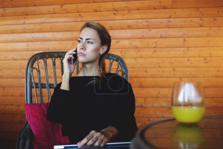 Serious woman entrepreneur is calling to client on mobile phone, while is waiting for him in cafe.
