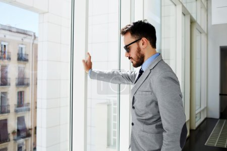 Confident male lawyer is thinking about future trial, while is standing in modern office interior.