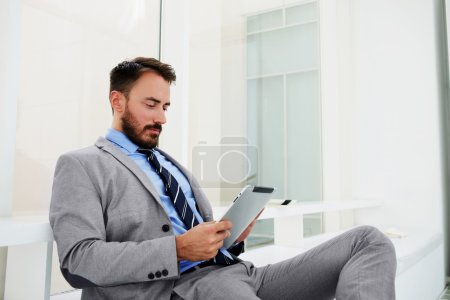 Man professional banker is checking the exchange rate in internet via digital tablet, while is sitting in modern office interior.
