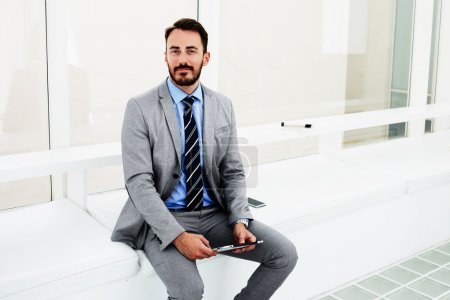 Intelligent man specialist in economics with digital tablet in hand sitting in office of successful company,
