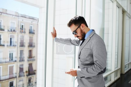 Man skilled CEO is searching information in internet via mobile phone before interview with new professionals.