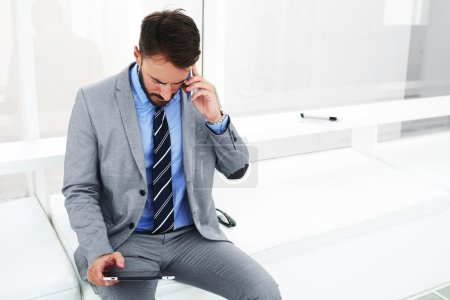 Man proud CEO is calling via cell telephone to his secretary during business trip abroad, while is booking hotel via touch pad,