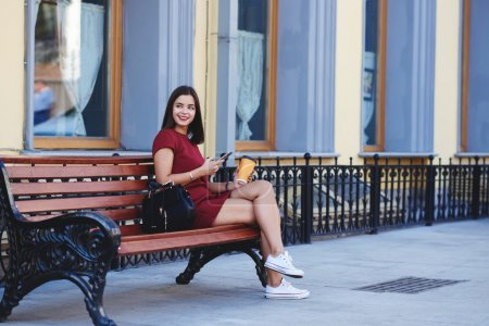 Happy woman is waiting call on her cellphone, while is relaxing outside with coffee