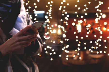 Closely image of young hipster girl is using her smart mobile phone, while is standing on the street against christmas garlands lights.