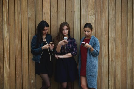 Young hipster girls dressed in trendy spring clothes are searching information on web page via their smart mobile phones
