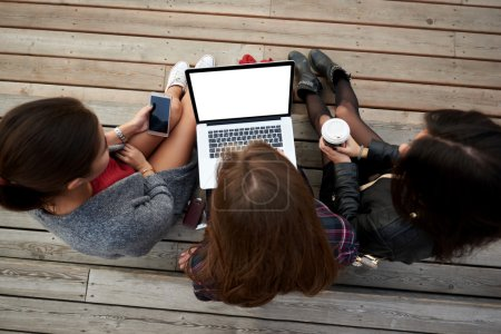 Top view of hipster girls are watching video in social network via portable net-book, while is sitting on a wooden stairs outdoors.
