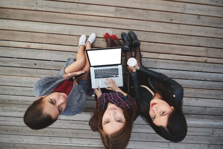 Top view of a three women are looking in camera, while sitting with laptop computer outdoors on a wooden stairs.