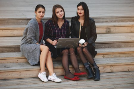 Young three hipster girls with trendy look are posing for camera after video call on net-book during their free time