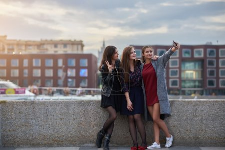Charming women are posing while making photo with cell telephone digital camera during their free time in weekend