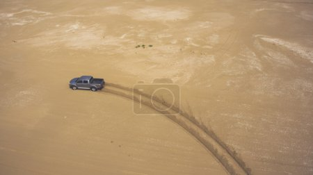 Aerial photo from flying drone of a riding pickup car in sandy dessert with copy space for your advertising text message or promotional content.
