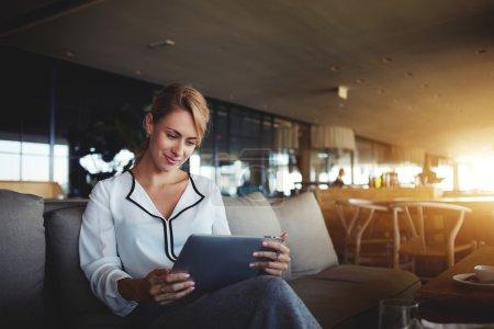 Female financier is reading financial news in internet via touch pad during work break in modern cafe