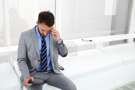 Man proud CEO is calling via cell telephone to his secretary during business trip abroad, while is booking hotel via touch pad