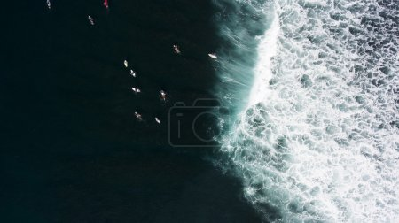 Top view from drone of a group of surfers seek to the ocean to catch next beautiful wave during surf lessons in Bali school