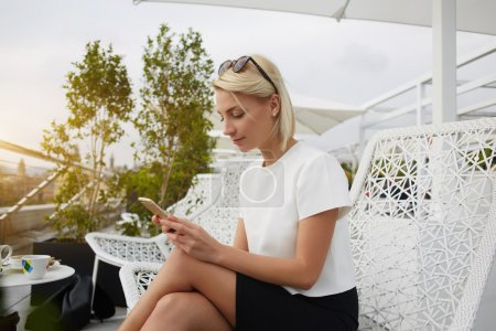 Female CEO is searching information in internet via cell telephone, while is sitting on hotel balcony.