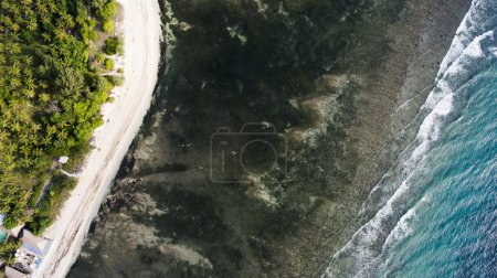 Top view aerial drone photo of an amazingly beautiful nature landscape with black color beach and sea turquoise water,