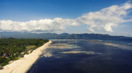 Aerial drone photo of beautiful coastline surrounded by a tropical landscape and jungle mountains.
