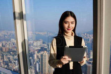 Young Asian woman is holding portable digital tablet