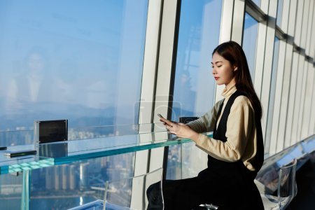 Young woman CEO is checking bank account via mobile phone