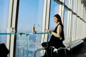 Asian entrepreneur woman is sitting in loft with contemporary interior and big window