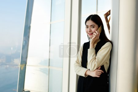 Young Japanese businesswoman is calling via mobile phone to her customer,