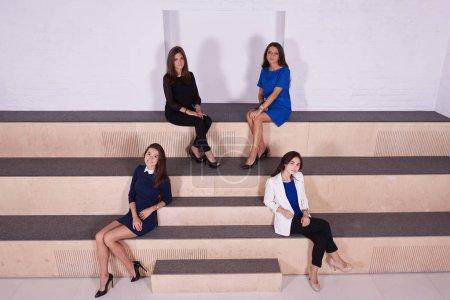 Four beautiful female dressed in elegant clothes