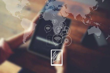 Photo pour Carte mondiale de la connexion réseau dans le design infographique. Mains masculines tenant tablette numérique, homme d'affaires naviguant sur Internet ou se connectant au sans fil via pavé tactile assis à la table en bois - image libre de droit