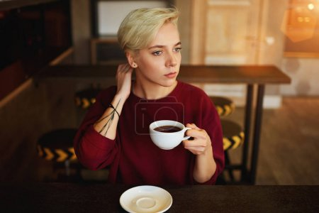 Female hipster drinking coffee and thinking over startup concept while
