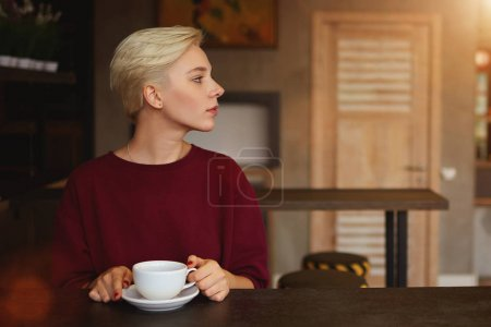 Hipster waiting for best friend meeting in modern cafe interior hanging cup of cappuccino