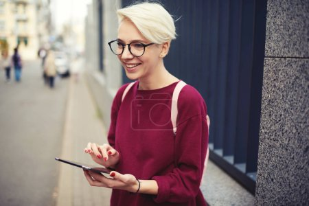 Smiling girl in stylish glasses having fun near copy space for advertising