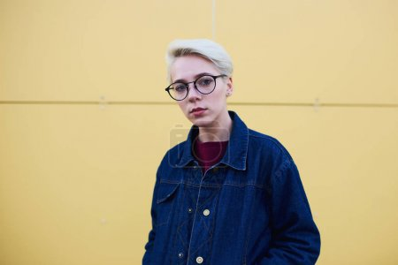 Hipster with natural makeup and short haircut dressed in casual jeans jacket and sweatshirt