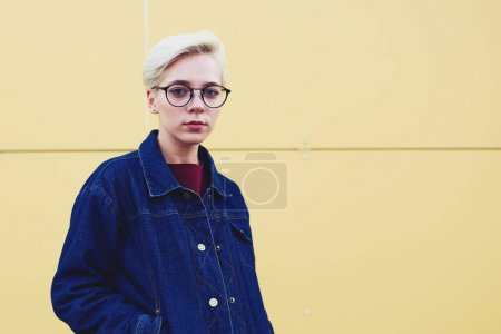 Young female teenager hipster with short hair cut and natural makeup walking on city street