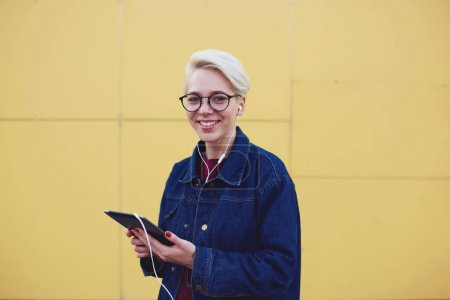 Likable woman using connection to internet while standing near copy space for your advertising