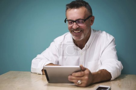 Male in trendy eyewearreading press release on web page of popular magazine