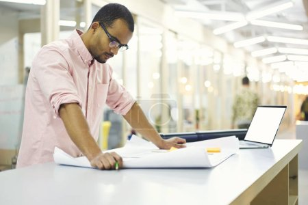 Man in office using laptop computer with mock up screen and wireless connection to internet in office indoor