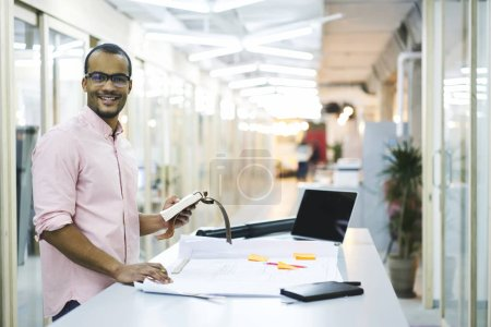 Smiling hipster  using laptop computer with blank screen connected to 5G wireless