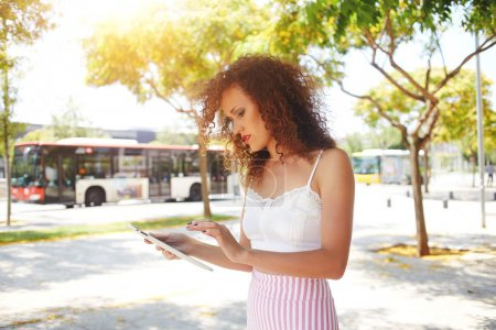 Serious woman standing on bus stop using free wifi connection near blurred background with copy space for advertising