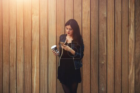 Beautiful female with take away coffee in hands typing text message to friend using a mobile phone.