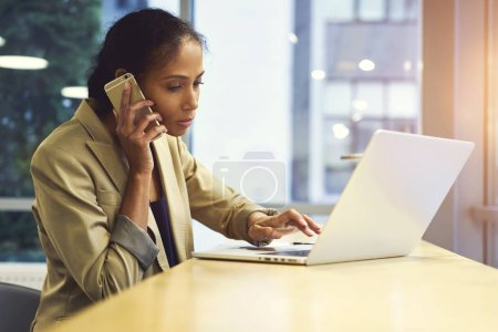 Single woman via modern laptop computer and wireless connection to internet sitting in office copy space for your advertising