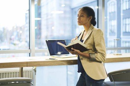 Photo pour Formal grave habillé attrayants afro américains femelles administratives faisant notes organisateur - image libre de droit