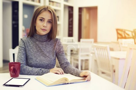 Beautiful female sitting at table in university library with free wifi zone drinking hot coffee for breakfast before starting lessons