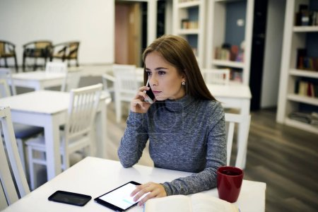 Likable girl  using touchpad and wireless connection for organizing work