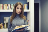 Serious female  checking each one from bookshelves in university modern library for students