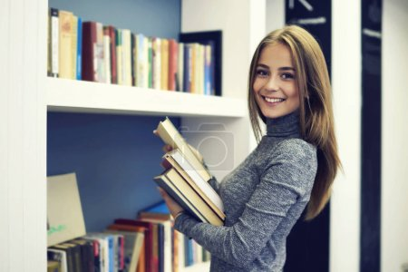 Young attractive cheerful female international student returning textbooks after passing annual exam putting them on bookshelves