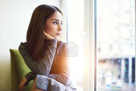 Photo pour Portrait de consciente séduisante jeune femelle obtenir inspirée par temps ensoleillé extérieur assis dans un café moderne intérieur près énorme espace fenêtre et copie pour votre publicité, à la recherche de suite - image libre de droit