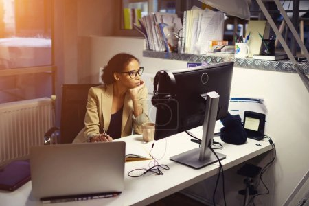 Young professional female journalist working hard staying in office at evening