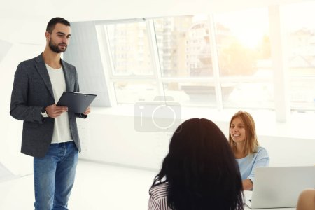 Bearded male entrepreneur speaking with group of talented marketing experts asking to create successful advertising campaign