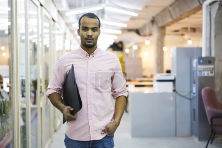 Serious man  holding file folder while standing in coworking office during work