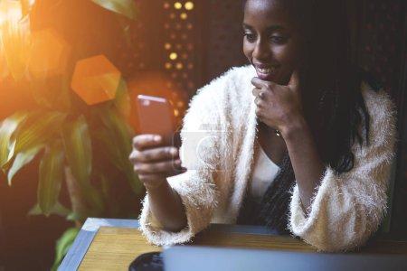 Photo pour Jeune modèle noir en tenue à la mode et de bonne humeur bavarder dans les réseaux sociaux en utilisant un appareil moderne, adolescent fille souriant tout en envoyant des commentaires pour les amis via smartphone assis dans un café à l'intérieur - image libre de droit