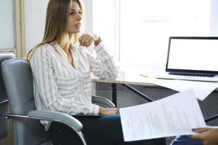 Photo pour Femme recruteur gestionnaire faire entrevue avec un jeune étudiant international sur la profession de graphiste poser des questions et lecture de papier cv assis dans le bureau de coworking à l'aide d'un ordinateur portable - image libre de droit